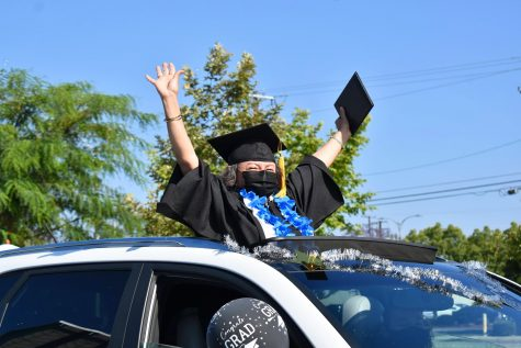 Cerritos College 2021 graduate ecstatically receives her diploma during a socially distanced commencement ceremony on May 28, 2021. Everyone in attendance is required to wear a mask.