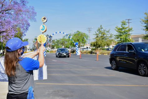 Staff, faculty and volunteers bang noise-makers and cheer as graduates drive by to receive their diploma on May 28, 2021. The CAR-MENCEMENT parade went from parking lot 10, to the front of the administration building.