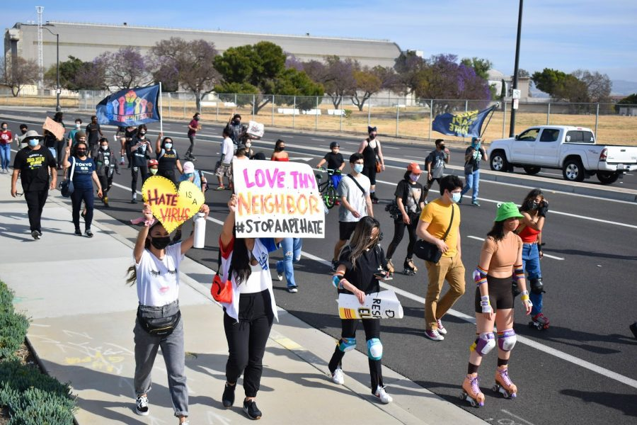 Marchers carry signs with messages of unity during the Skate to End Hate protest in Tustin on May 1, 2021. The protest was in response to the rise in AAPI hate crimes and the assault on Jenna Dupuy.