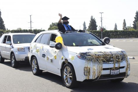 A graduate waves from the sunroof of her vehicle for the first ever Car-mencement on May 28, 2021. Cars lined up in lot 10 before driving along the celebratory track.