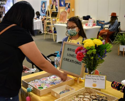 """Mia Mateos, 8, sells her handcrafted jewelry from her business """"Bright Lovely Creations,"""" during a pop-up event in Norwalk Town Square on May 15, 2021. She made the jewelry using beads, and sold stickers as well."""