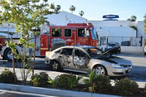 A Chevy sedan catches fire across the street from Norwalk Town Square on April 29, 2021. LA County Fire Station 20 arrives quickly to extinguish the flames.