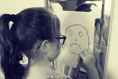Little girl draws a sad face on a paper in front of her mirror. This facial expression represents how she is feeling in the moment.