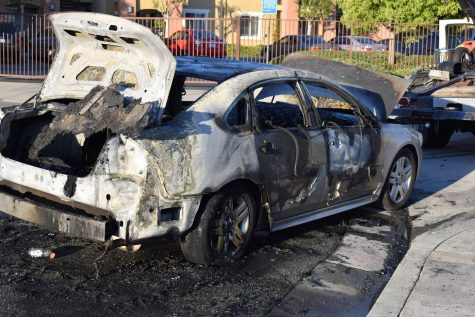 A Chevy sedan burns after a speaker in the trunk catches fire. The vehicle burns across the street from the Norwalk Town Square on April 29, 2021.