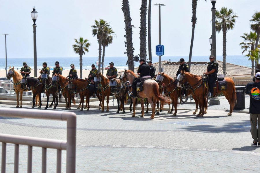 Huntington Beach Police sit on horseback during a protest on April 11. They arrested several protesters on the Huntington Beach Pier.