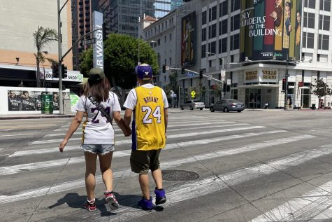 Tourist couple walking north from the Staples Center on Kobe Bryant day. They are crossing the sidewalk together wearing matching Kobe jerseys.