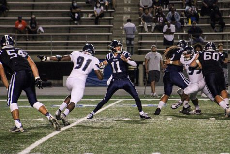 Cerritos Sophmore Quarterback Cade McConnell #11 drops back in the pocket to pass while being hurried by a Fullerton Defensive Lineman in the Fourth Quarter. Photo By: Roman Acosta Staff Writer for the Talon Marks, Sept. 11th, 2021.