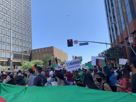 """Afghans, Afghan Americans, and allies march on Willshire Blvd in Los Angeles, Calif. demanding Congress members and President Biden to extend the evacuation of Afghans until Aug. 31st. Protestors on Aug. 28th hold a poster saying """"Zindabad Afghanistan"""" which translates to """"long live Afghanistan""""."""