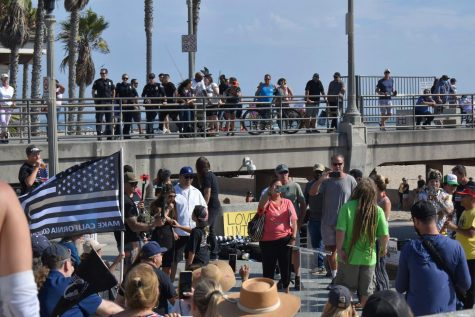 Police watch the Freedom Rally from Huntington Beach on Aug. 29, 2021. Protestors curse and yell at the police while waving blue lives matter flags.