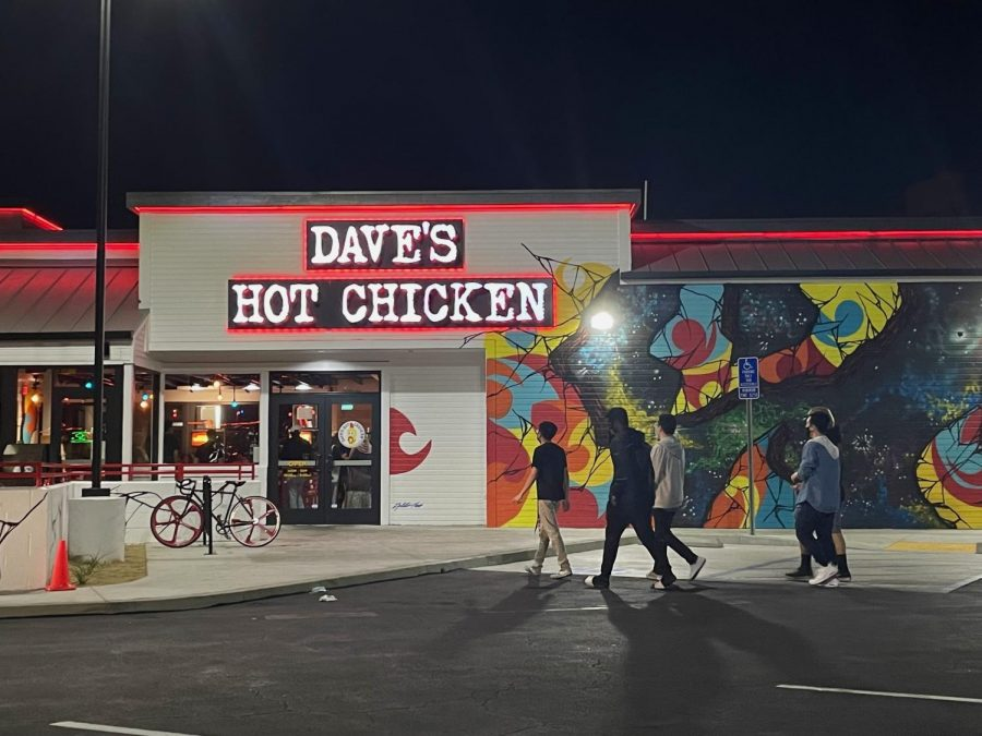 Customers+walk+to+the+new+Daves+Hot+Chicken+location+which+opened+on+Sept.+12.+There+were+busy+lines+inside+the+red-lit+store+with+customers+eager+to+try+spicy+chicken.+Photo+credit%3A+Fatima+Durrani