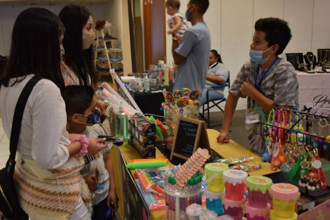 Jaden Avila, 10, sells his products to customers during a small business pop-up event on Aug. 28, 2021. He sells slime, key chains and toys at his business, Jaden