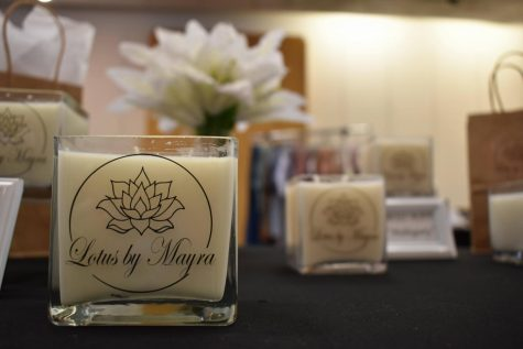 Mayra Rojas-Narrete sells candles at her business, Lotus by Mayra, during the final small business pop-up shop at the Norwalk Town Square on Aug. 28, 2021. The pop-up shops are moving to another location to accommodate more businesses.
