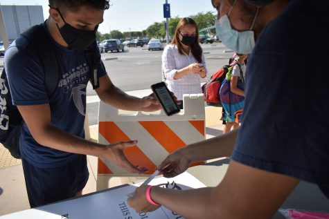 Shawn Martinez receives a wristband after passing the questionnaire at the health screening kiosk. Athletes are required to receive weekly COVID tests, as the 29 case of COVID-19 was found at the college on Aug. 9, 2021.