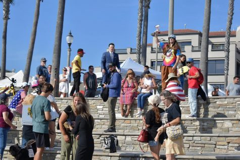 """A man in a blue suit tells supporters to take to the streets and """"raise some hell,"""" during the end of the Huntington Beach Freedom Rally on Aug. 29, 2021. He said to one supporter, """"we&squot;re going to take the plaza."""""""