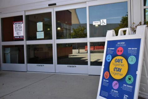 Signs are placed outside Cerritos College buildings and facilities reminding everyone to wear a mask and get vaccinated. The Cerritos College Board of Trustees proposed revisions to the vaccine mandate policy during their meeting on Sept. 15, 2021. Photo credit: Vincent Medina