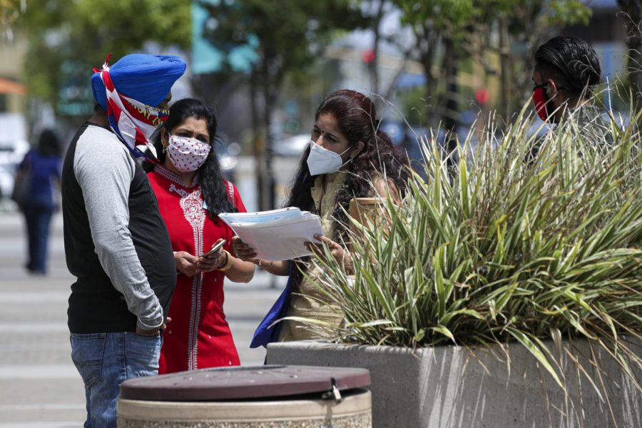 Payal Sawhney, right, and Raji Satish, middle, talk about the COVID-19 vaccine with a passerby on Pioneer Boulevard in Artesia, Calif. (Irfan Khan/Los Angeles Times/TNS)