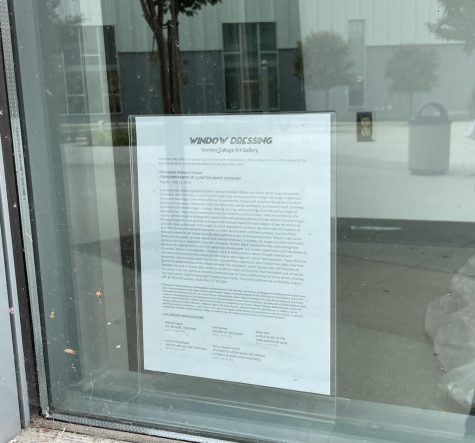 Information regarding the window dressing featuring Velasco's Forbidden Photos Of A Doctor Above Suspicion is displayed on a window of Fine Arts building. Below the context & background of Velasco's work lists upcoming installations.